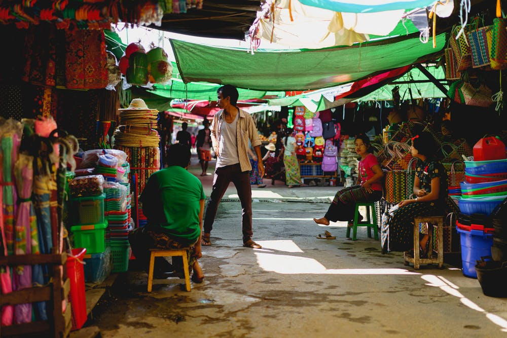 Man standing among market vendors under green tarps at the village market of Nyaungshwe Myanmar