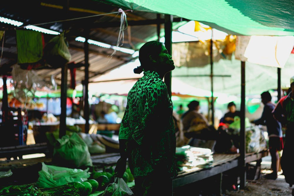 Burmese woman standing under green tarps of village market in Nyaungshwe Myanmar
