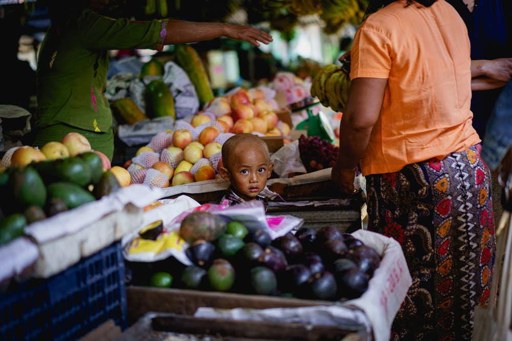 Young Burmese boy with shaved head standing among boxes of food at the village market in Nyaungshwe Myanmar