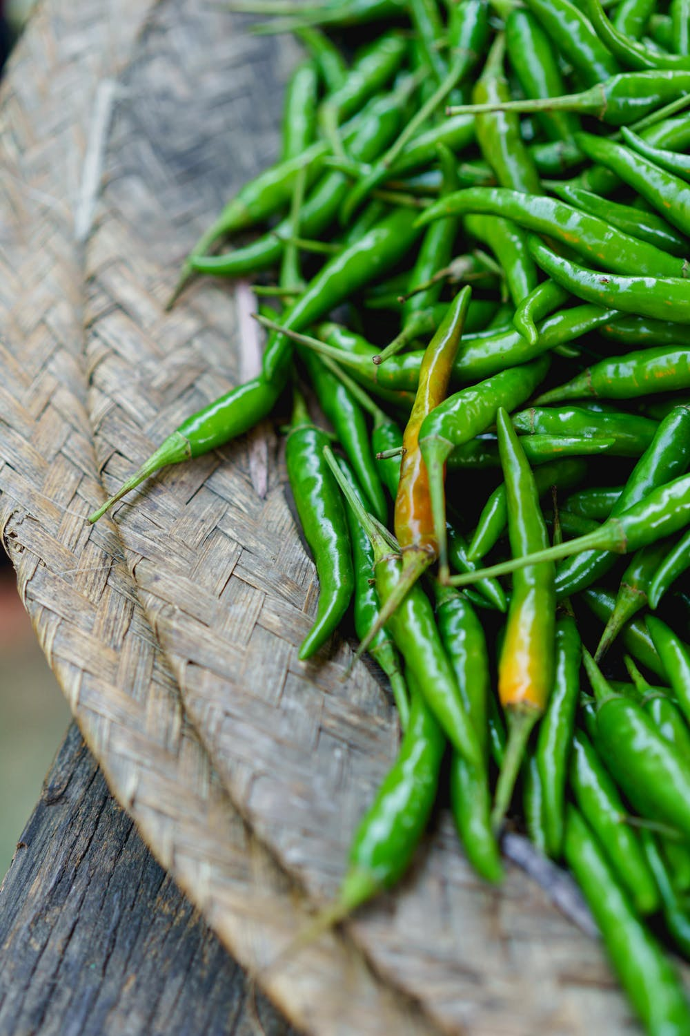 Bright green chili peppers for sale on a woven mat in the village market of Nyaungshwe Myanmar