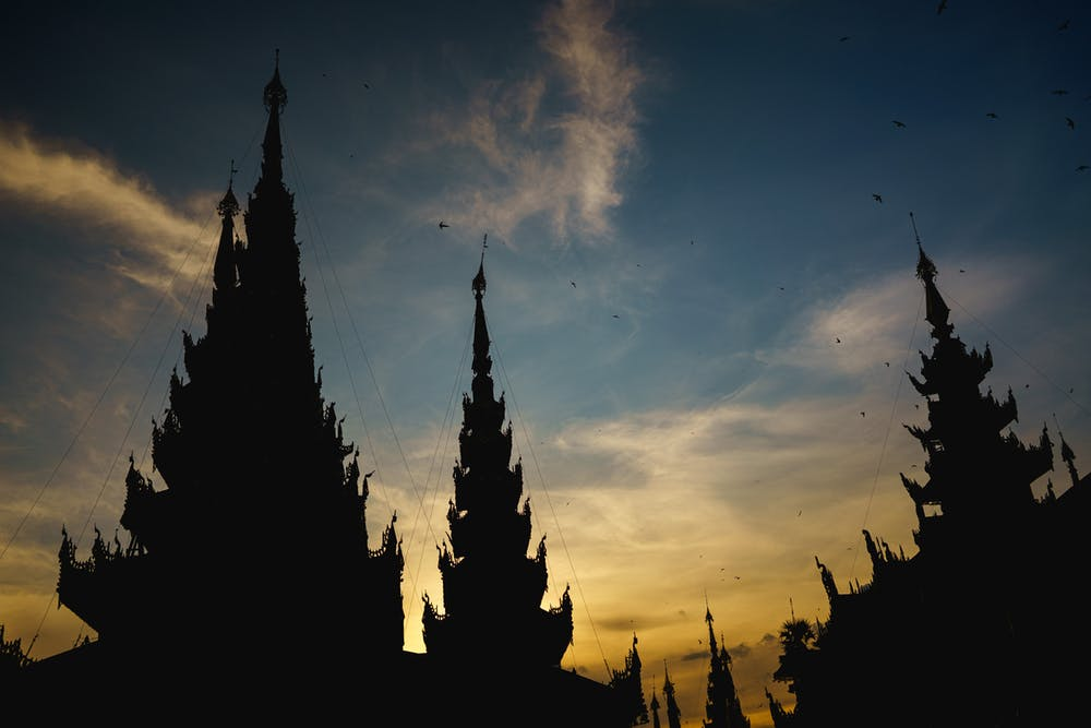 Spires of Buddhist shrines against a sunset sky in Yangon Myanmar at Shwedagon Pagoda