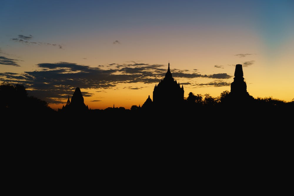 Outlines of Buddhist temples against a vibrant sunrise sky at the national park of Bagan Myanmar