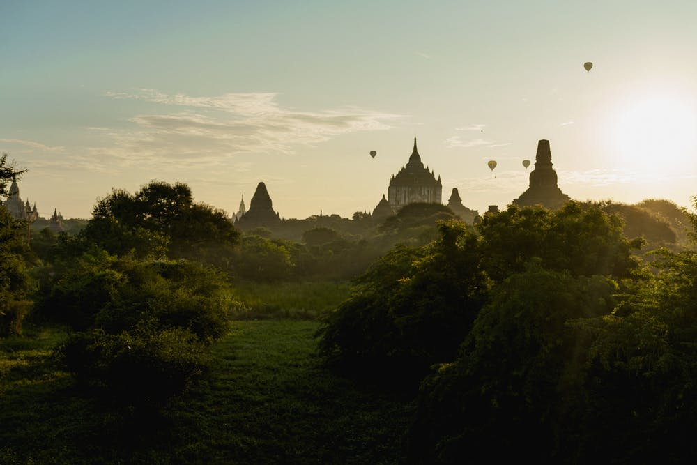 Layers of trees and Buddhist temples against the sky during sunrise at Bagan Myanmar