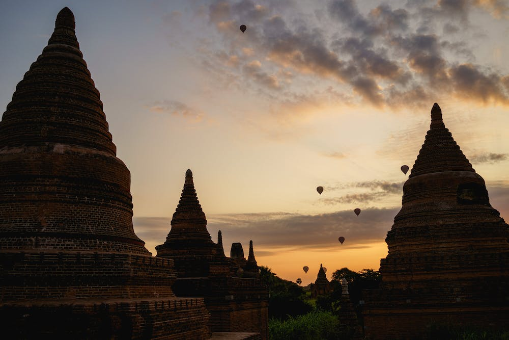 Hot air balloons going up at sunrise against a backdrop of Buddhist temple and pagoda silhouettes in Bagan Myanmar