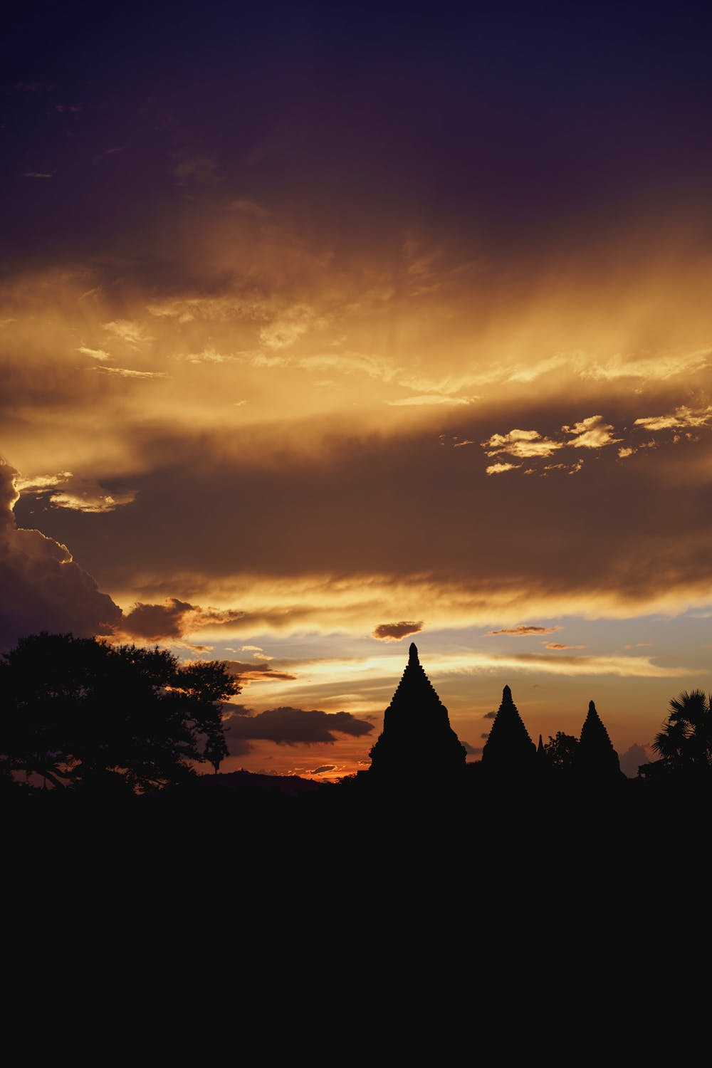 Waves of clouds across the sky during sunset with three stone pagodas at the horizon