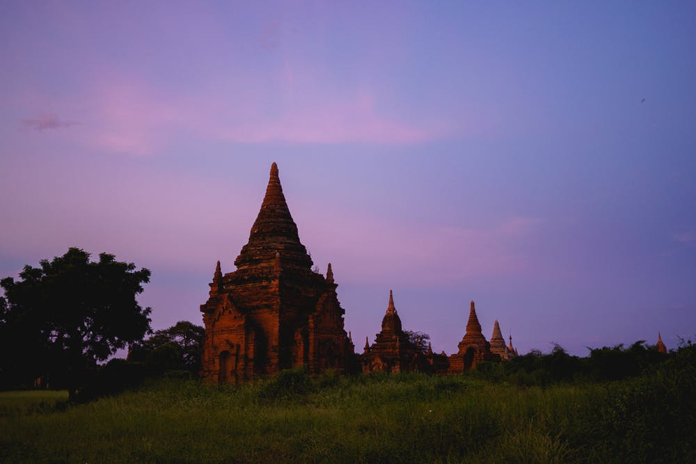 Pink and purple sunset sky with a view of several red stone pagodas in Bagan Myanmar