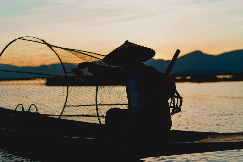 Dancing fisherman of Inle Lake Myanmar sitting on a boat at sunset with a circular fishing net and fishing hat