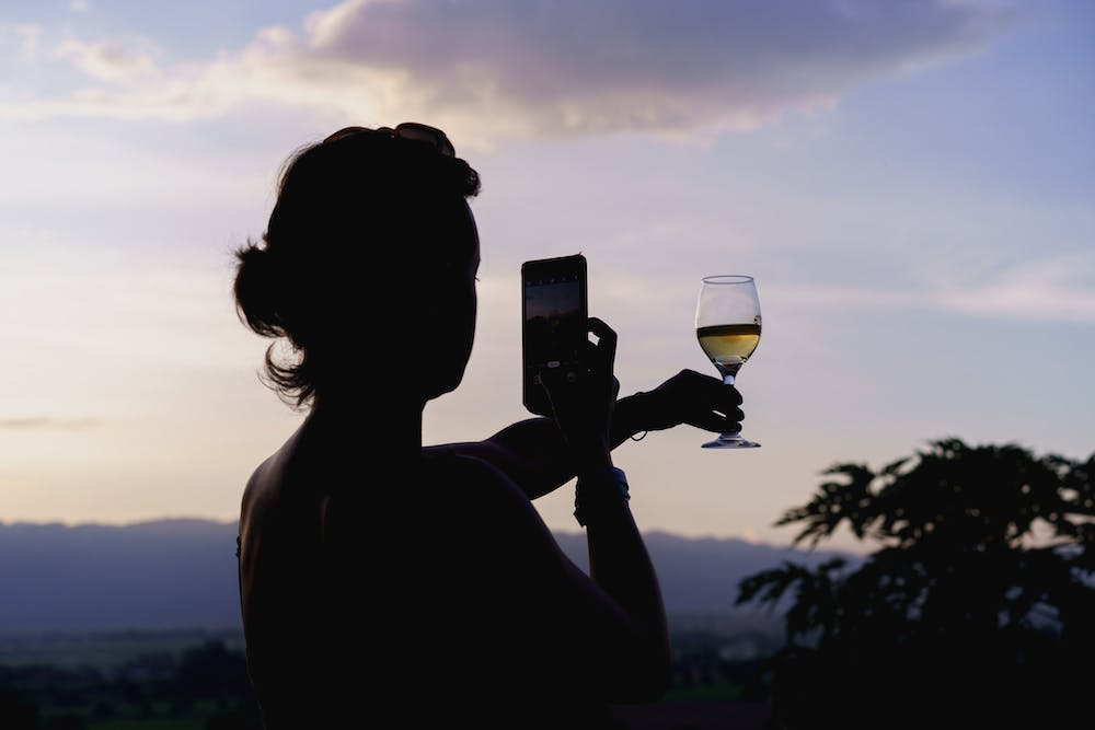 Girl taking a photo of a wine glass against a sunset backdrop with a cell phone camera in Myanmar