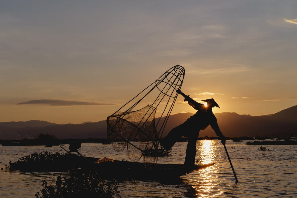 Magic golden hour at Inle Lake Myanmar as a dancing fisherman is balancing on one foot in his boat