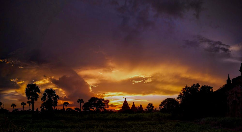 Magical multicolored sunset sky behind the pagodas at the horizon in the Bagan national park of Myanmar