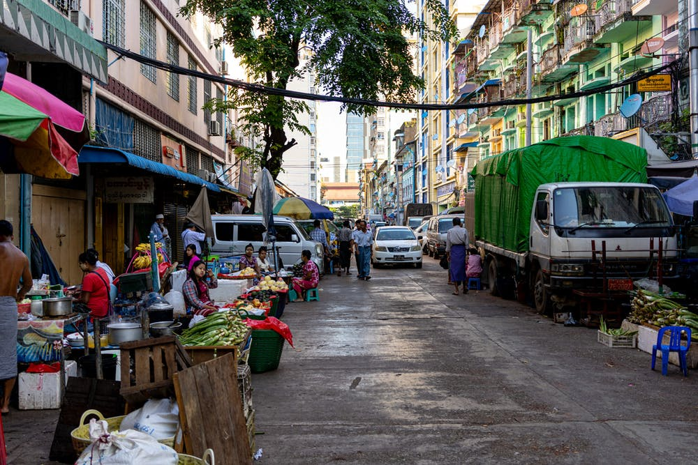 A street market on a local street with pastel colored buildings in Yangon Chinatown