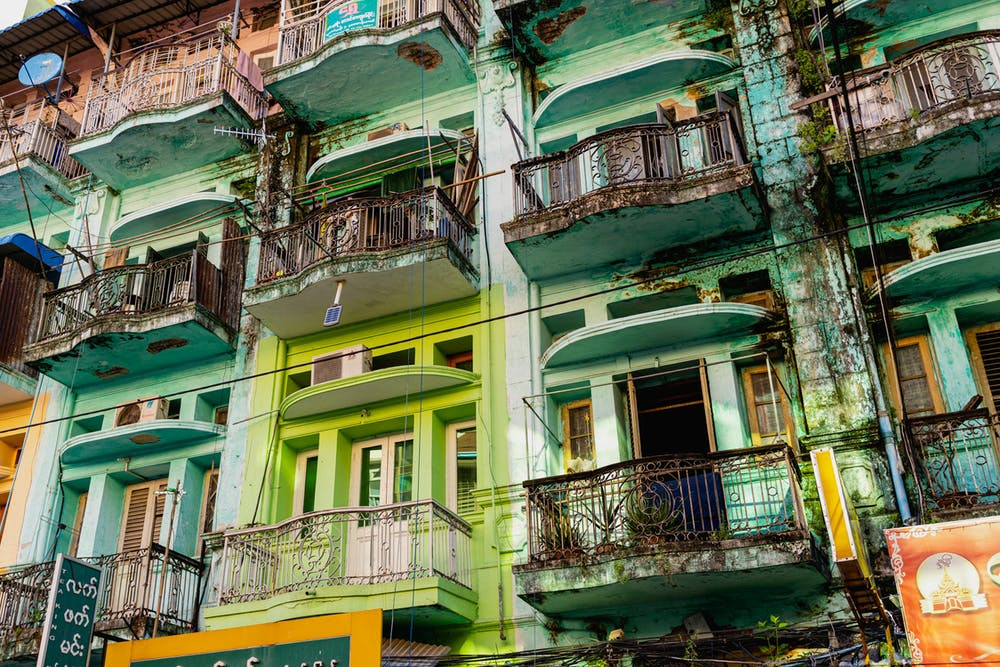 Crowded and old pastel colored building facades with balconies in Chinatown of Yangon Myanmar