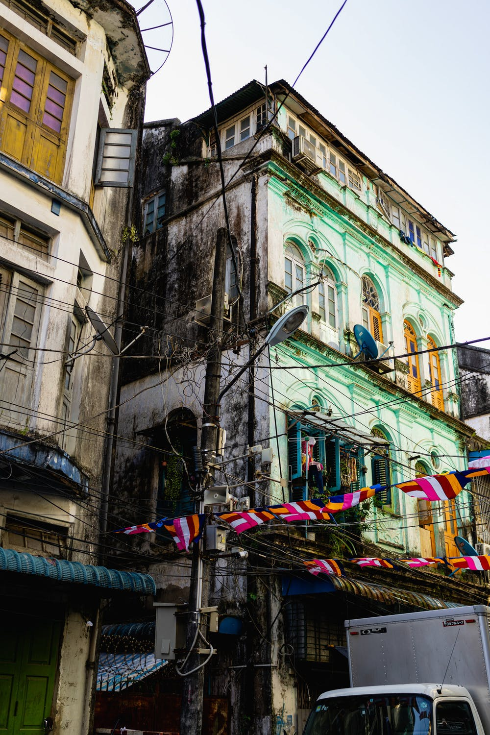 Old colonial architecture on a pastel colored building on a local street in Chinatown of Yangon Myanmar