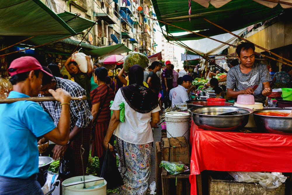 Woman carrying a bundle on her head at a busy crowded street market in Chinatown of Yangon Myanmar