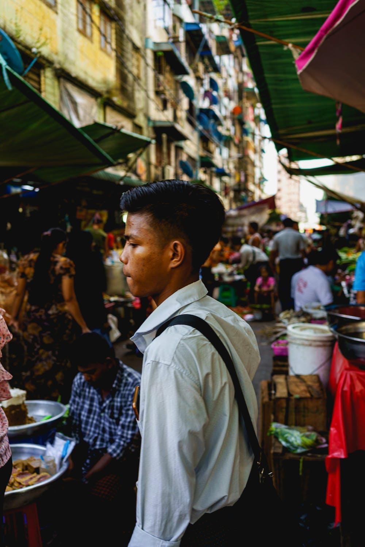 Burmese school boy in uniform crossing the street market of a busy road in Chinatown of Yangon Myanmar