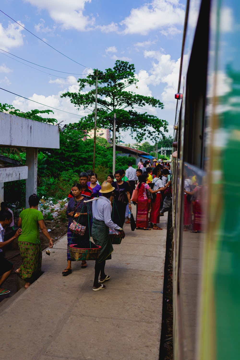 Lower-class Burmese locals wait on the train platform for the circle line Yangon metro in Yangon Myanmar