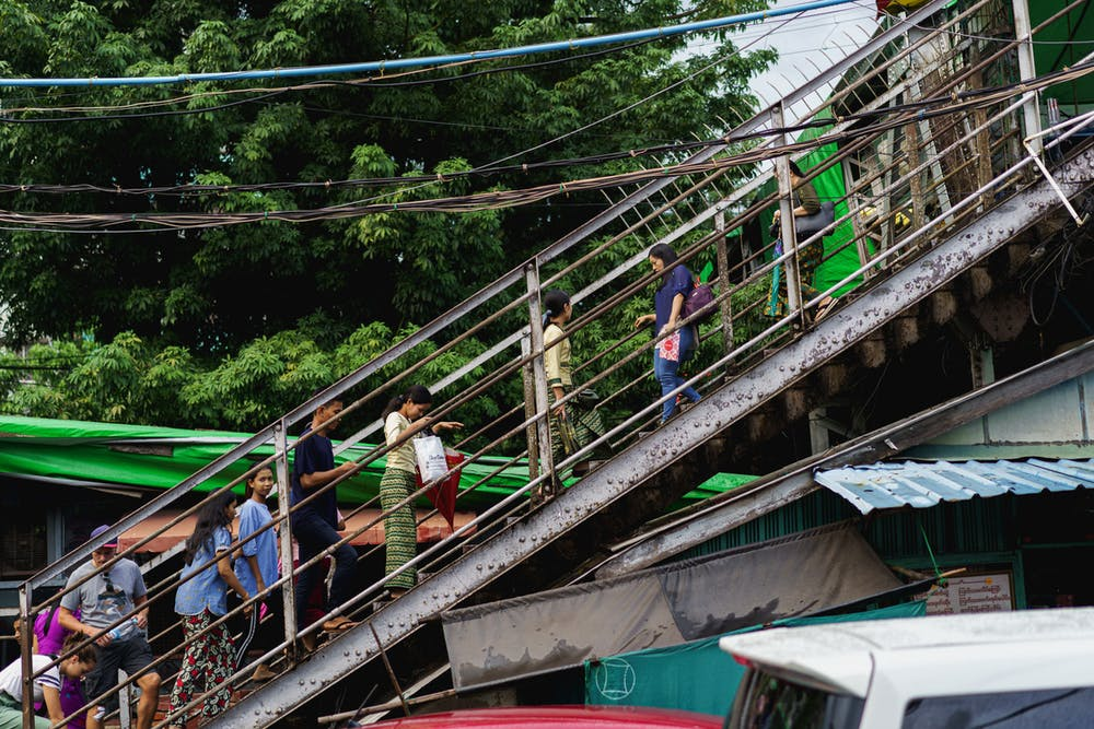 Burmese locals walking down a stairwell of an elevated pedestrian walkway at a crossroads in Yangon Myanmar