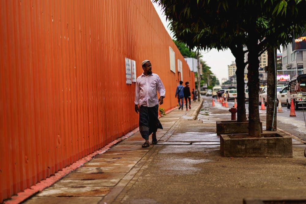 Men in longyi walking past a construction site in downtown Yangon Myanmar