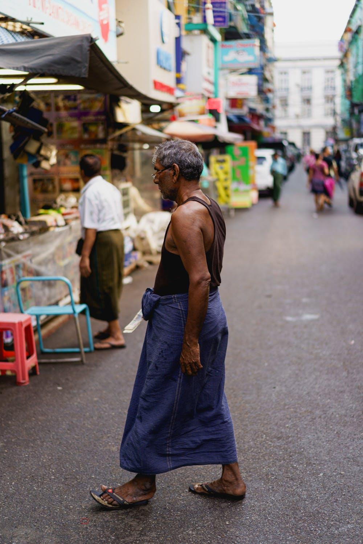 Local Burmese man wearing traditional dress of a longyi in downtown Yangon Myanmar