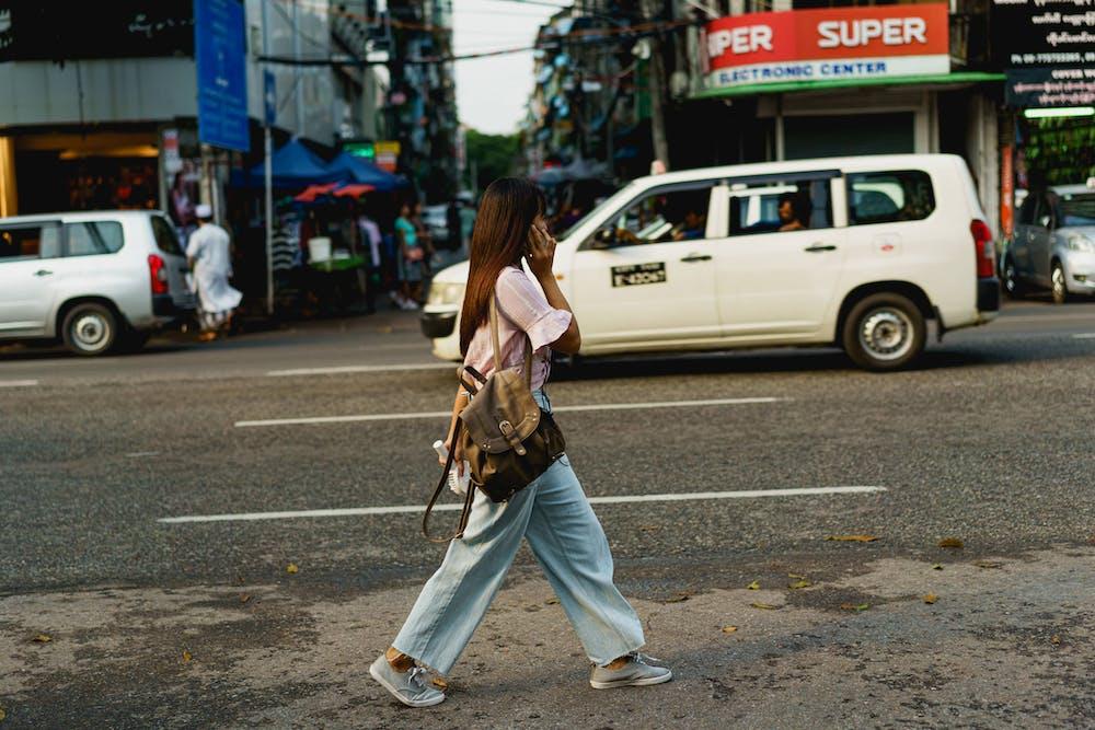 Modern Burmese woman walking down a busy street at golden hour in Yangon Myanmar