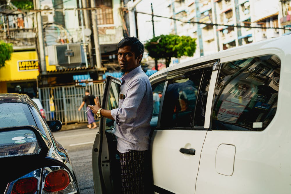 Local Burmese man holding a car door open with cigarette in hand at rush hour in Yangon Myanmar