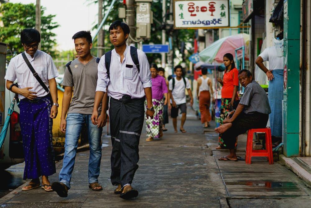 Young men in traditional and modern dress walk down a neighborhood street in Yangon Myanmar