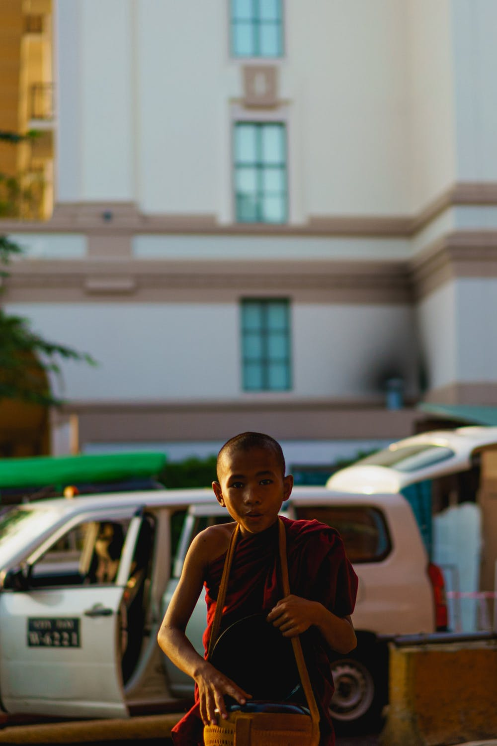 Young Burmese Buddhist monk carrying a bag and walking in Yangon Myanmar