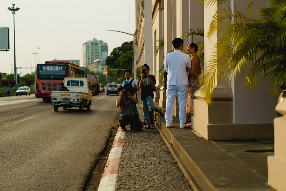 Wealthy Burmese couple taking engagement and wedding photos outside famous hotel in Yangon Myanmar