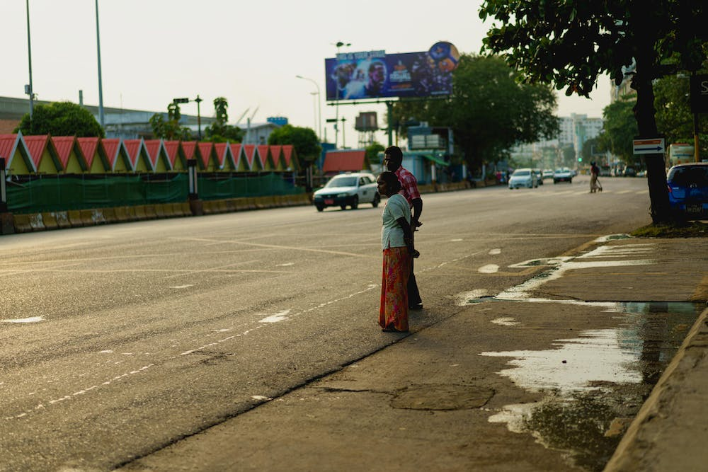 Indian Burmese locals wait to cross the street at a busy road in Yangon Myanmar