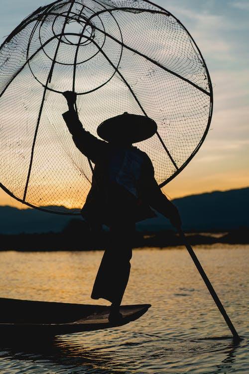 Inle Lake Myanmar'da büyük geleneksel balık ağı ile ünlü dans eden Birmanyalı balıkçılar