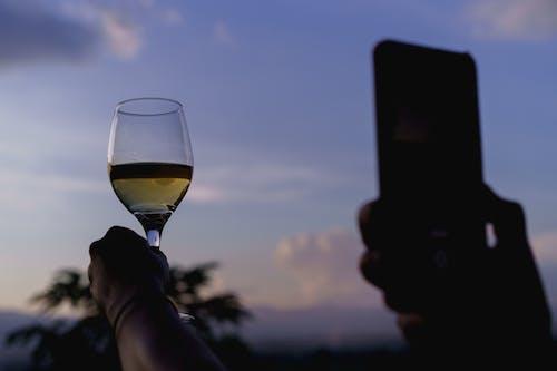 Myanmar Inle Gölü yakınlarında bir bardakta şarap dolu bir telefonla fotoğraf çekmek