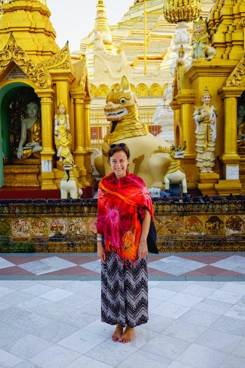 Shwedagon Pagoda Yangon Myanmar Burma'da kırmızı ve turuncu Malaya peştemâli giyen kız omuzlarını örtüyor