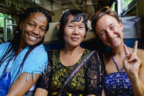 Yangon Circle Line Tren Myanmar Burma'da fotoğraf çeken Birmanyalı kadınla gezen sırt çantalı gezgin kızlar
