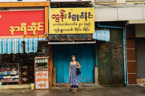 Yangon Myanmar Burma şehir merkezinde Birmanya işaretleri ve yerel dükkanlarla duran gezgin kız