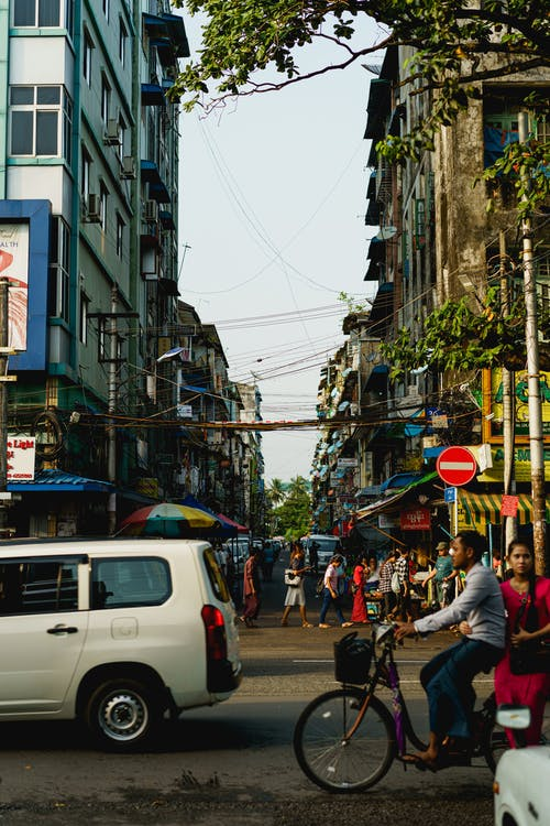 Yangon Myanmar Burma şehir merkezinde işlek caddeden geçen arabalar ve bisikletler