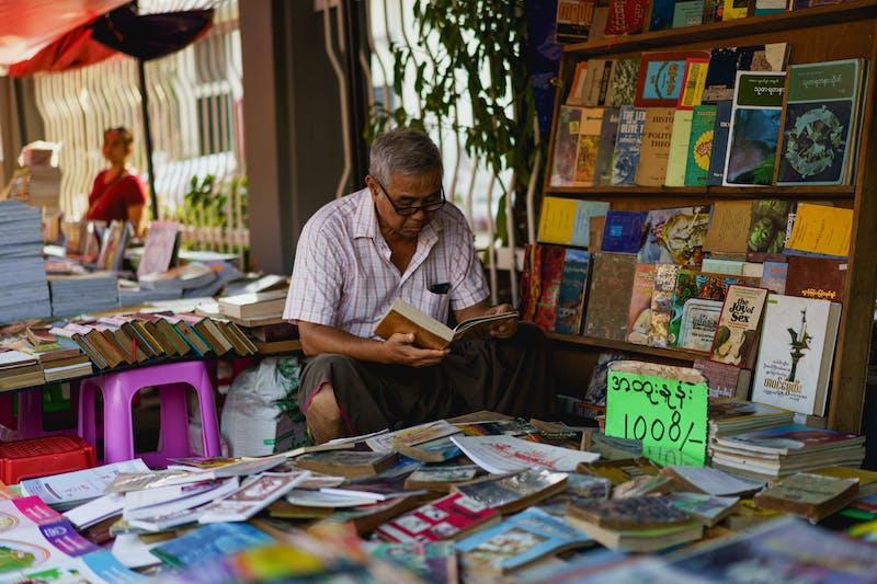 Sekreterlik şehir Yangon Myanmar Burma yakınlarındaki hafta sonu kitap pazarında kitap satan Birmanyalı adam