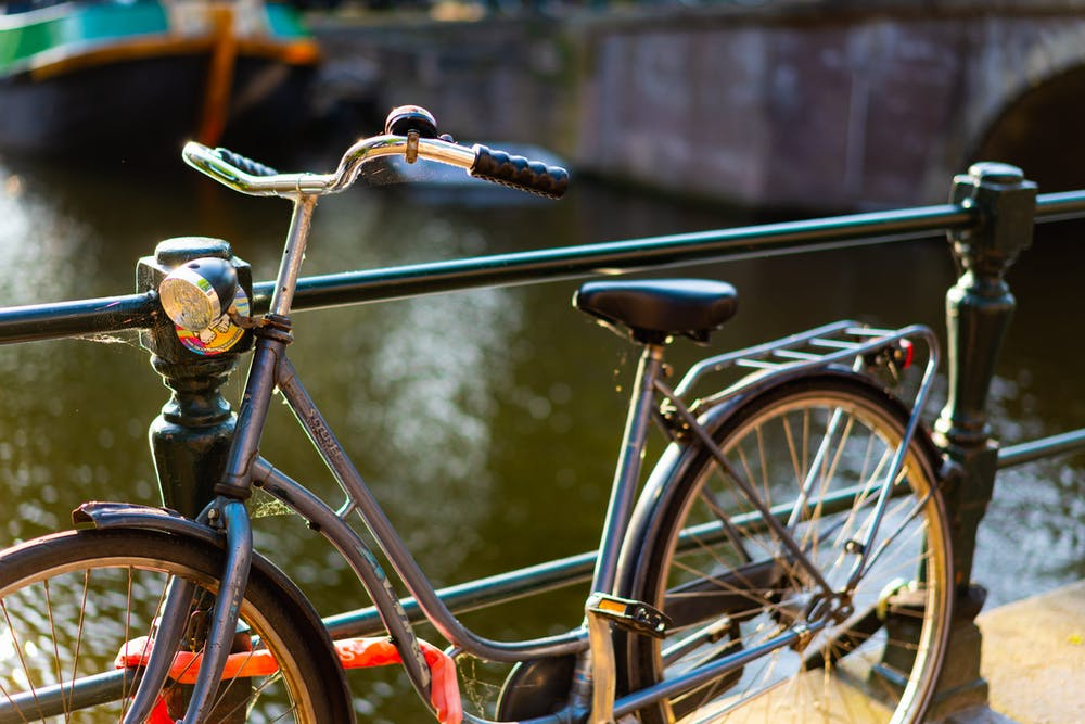 Old bike along a canal railing in Amsterdam