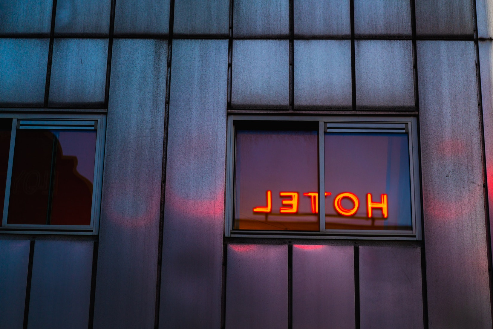 Neon lights of HOTEL reflecting in a window