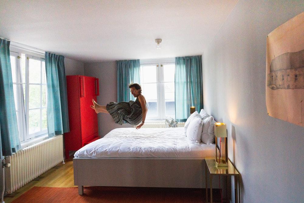 Girl jumping on bed at Lloyd Hotel, Amsterdam