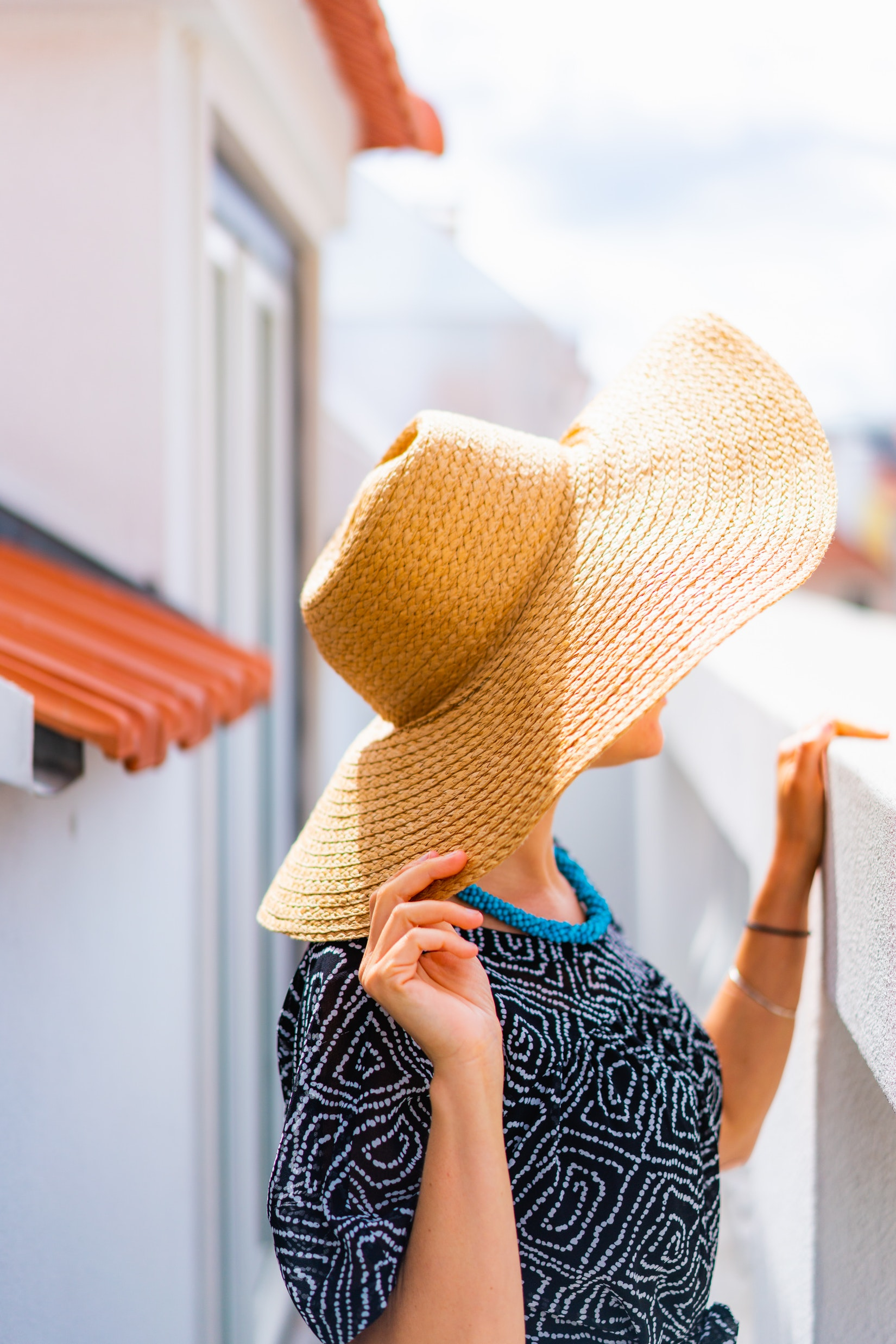 Girl with a sunhat looking over a balcony at The Lisboans in Lisbon, Portugal