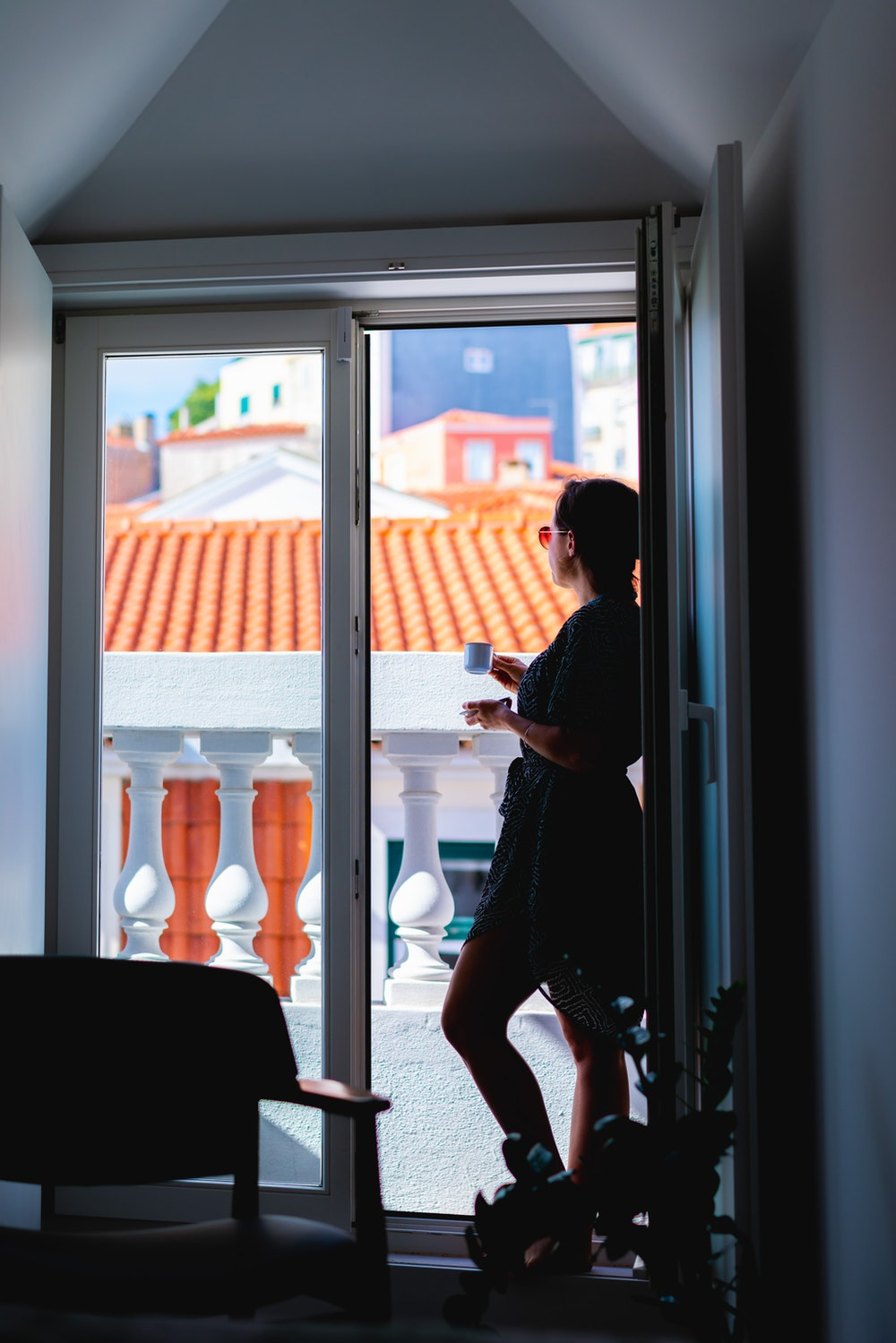 Girl drinking tea while looking out a window at The Lisboans in Lisbon, Portugal
