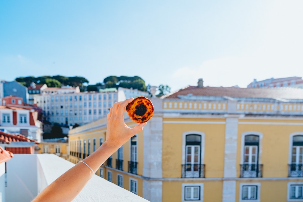 Holding up a pastel de nata with the view at The Lisboans in Lisbon, Portugal