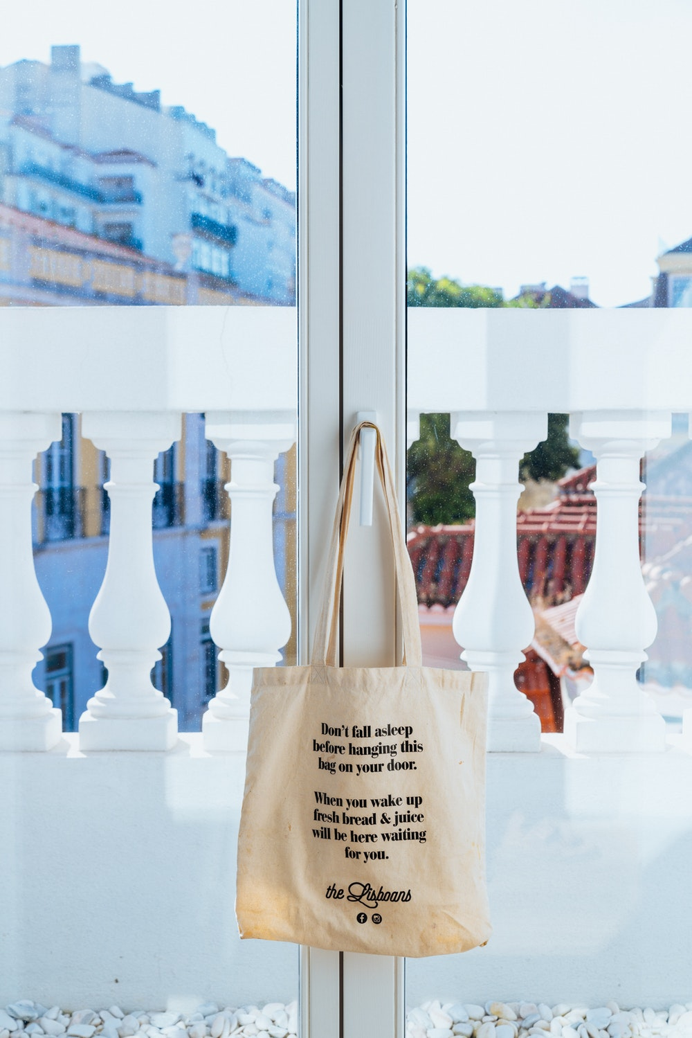 Tote bag hanging on glass doors at The Lisboans in Lisbon, Portugal