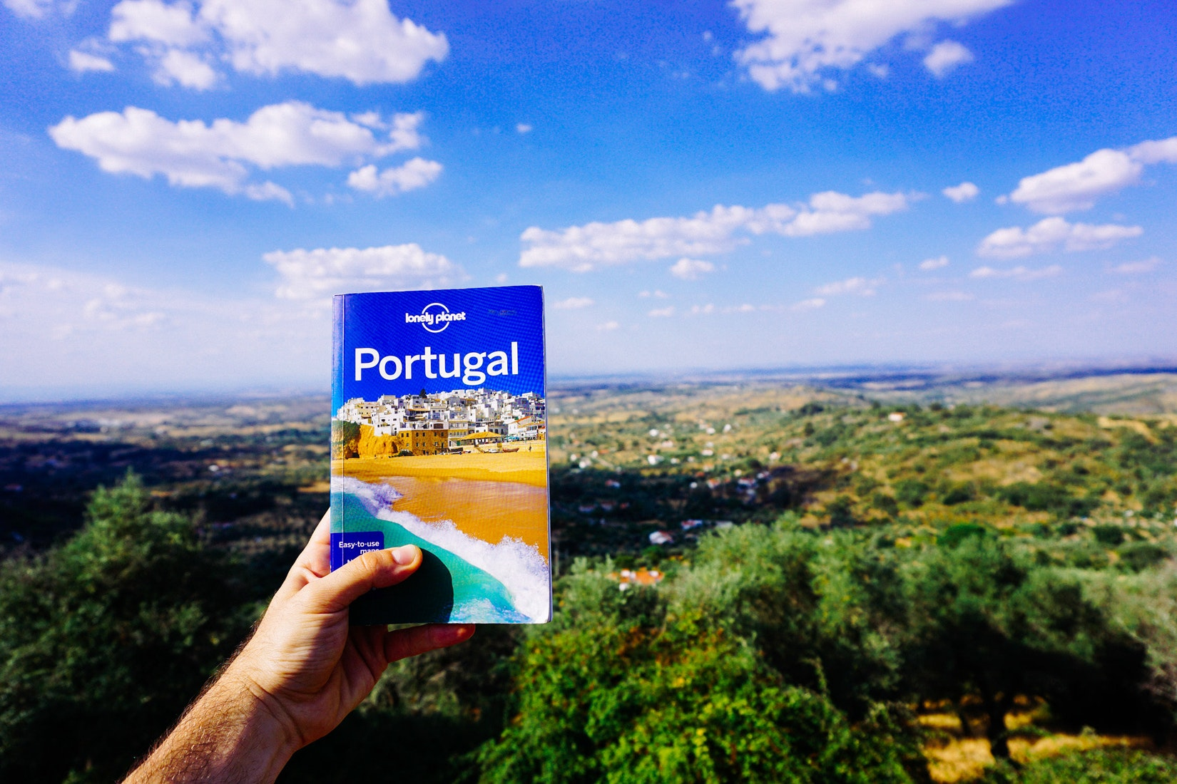Holding up our Lonely Planet Portugal book in Castelo de Vide
