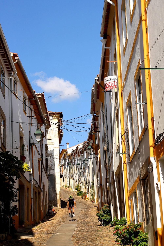 A hilly street with a biker in Castelo de Vide