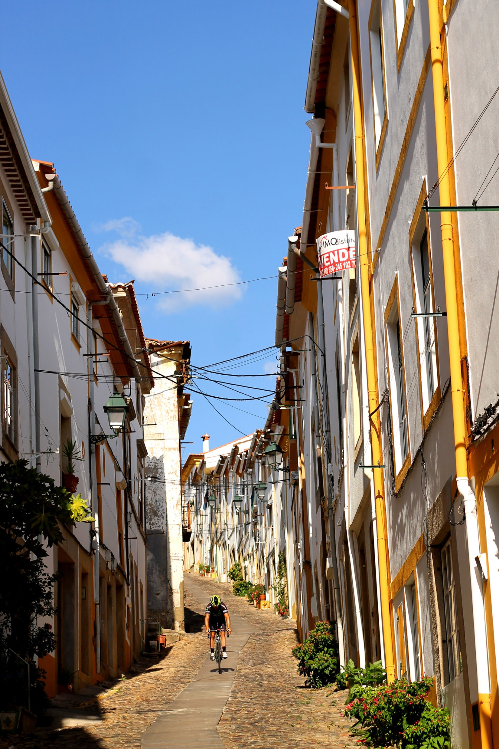 A hilly street with a biker in Castelo de Vide