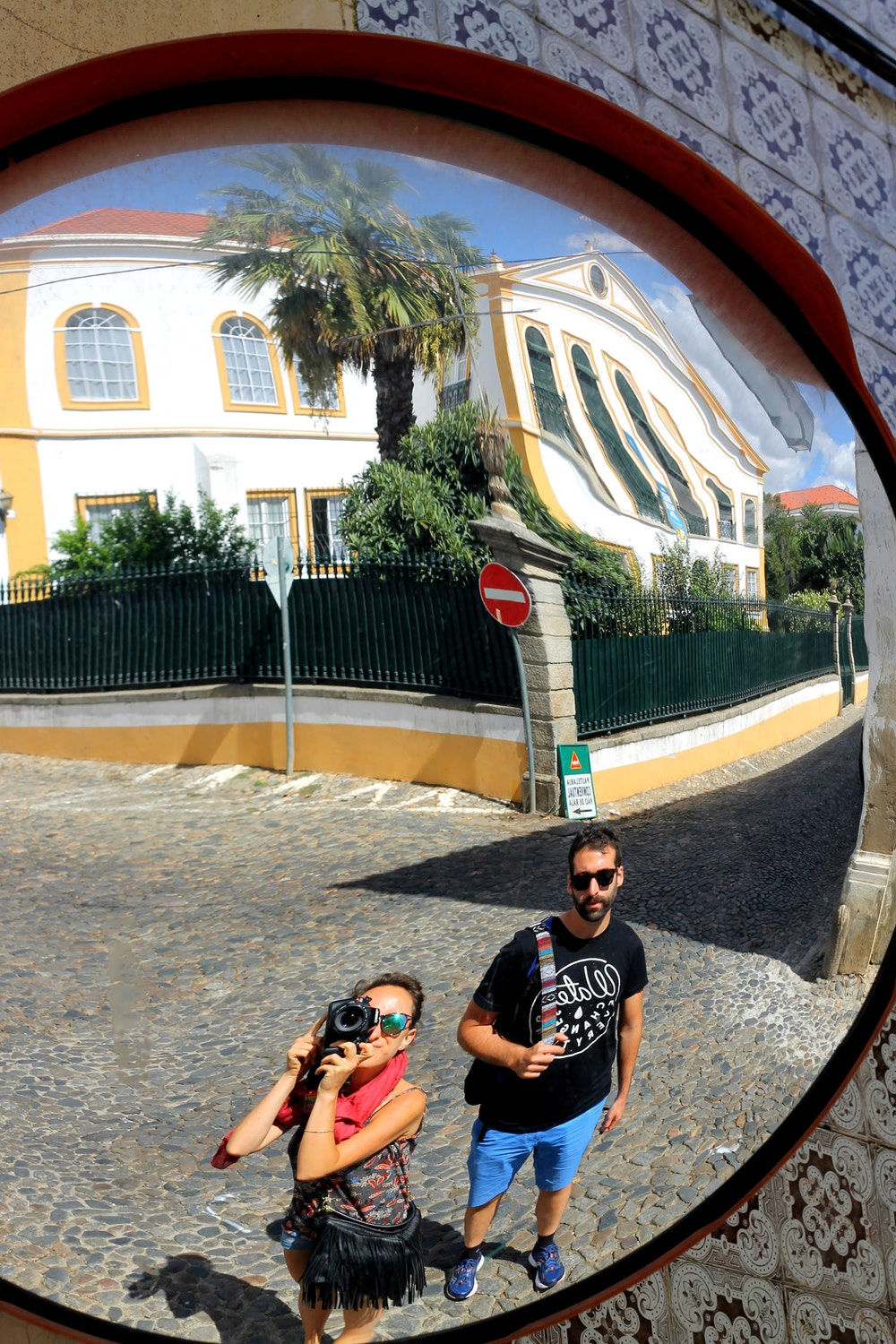 Taking a photo in a mirror on a quiet street in Evora, Portugal