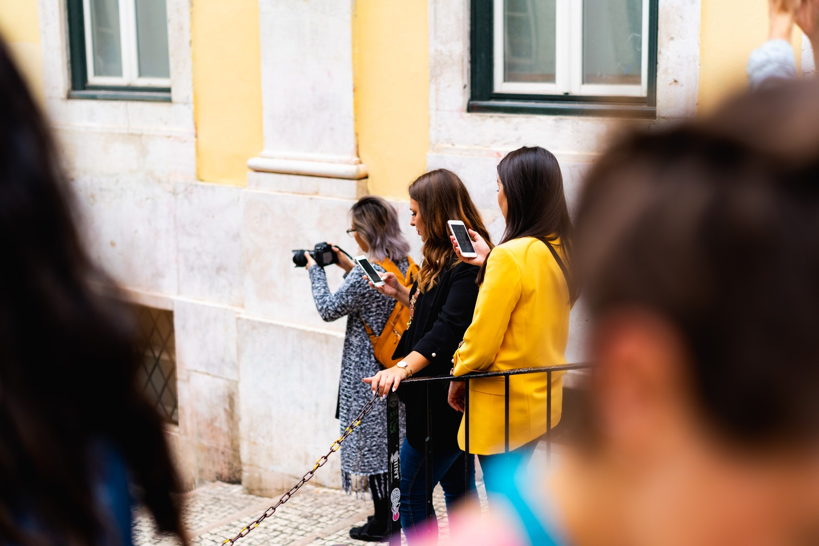 Girls each taking a photo on Rua de Bica in Bairro Alto, Lisbon, Portugal