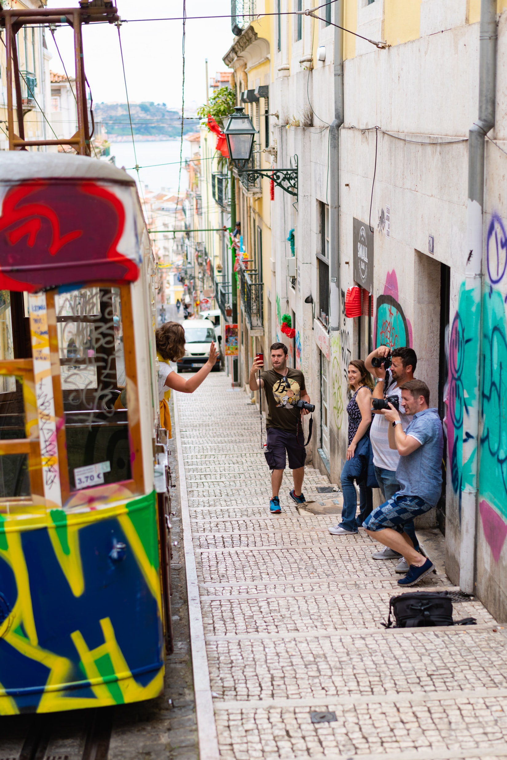 People aking photos of the old streetcar on Rua de Bica in Bairro Alto, Lisbon, Portugal