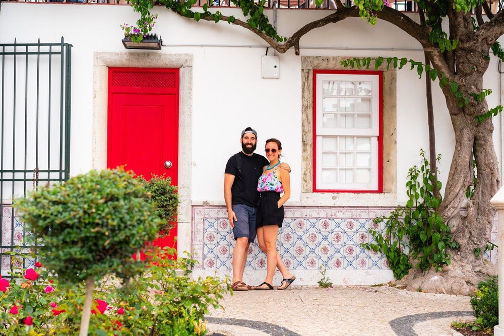 Becca and Dan with a quaint wall in the park of Miraduoro de Santa Luiza in Lisbon, Portugal